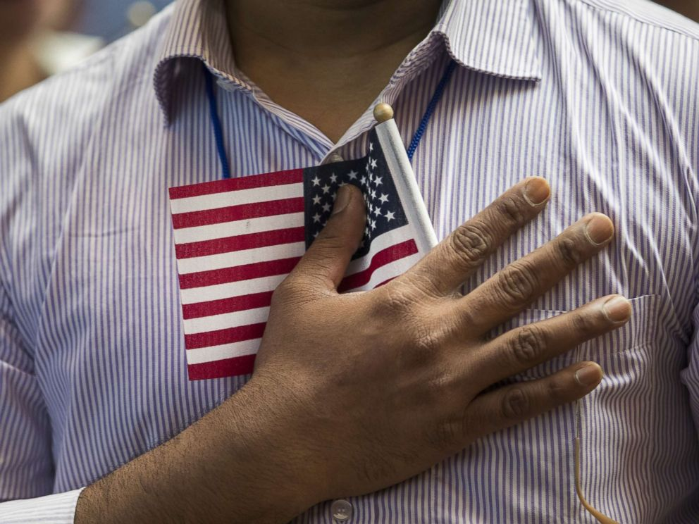 PHOTO: A new U.S. citizen holds a flag to his chest during the Pledge of Allegiance during a naturalization ceremony at the New York Public Library, July 3, 2018, in New York.