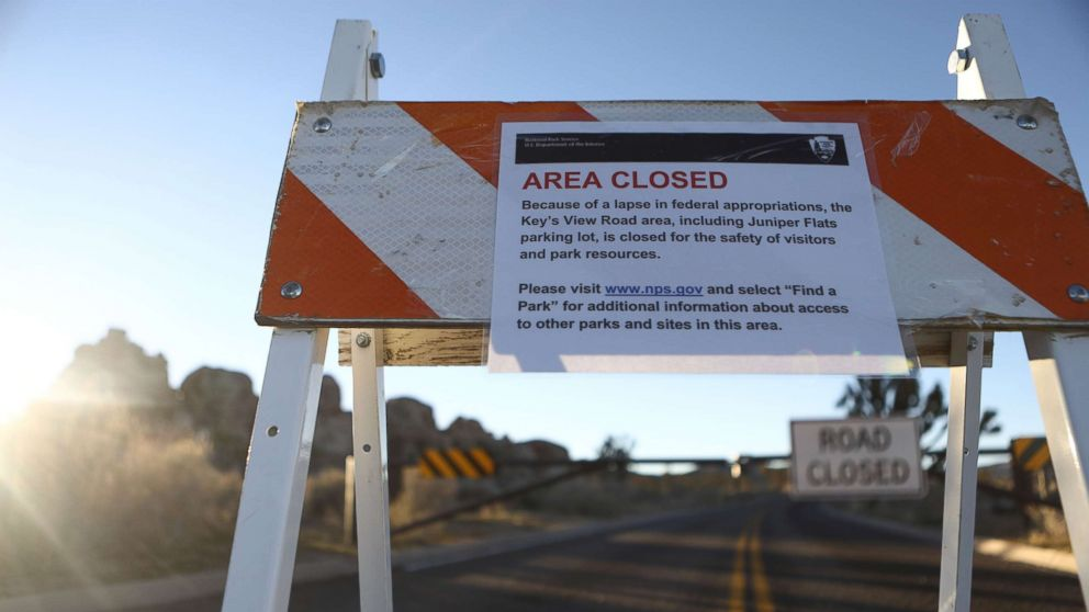 An 'Area Closed' sign is posted in front of a closed section of road at Joshua Tree National Park, Jan. 4, 2019, in Joshua Tree National Park, Calif. Campgrounds and some roads have been closed at the park due to safety concerns as the park is drastically understaffed during the partial government shutdown.