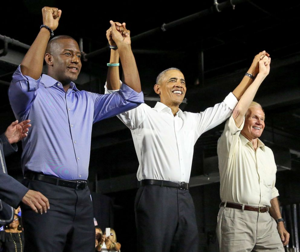 Andrew Gillum, Democratic nominee for governor of Florida, former President Barack Obama and U.S. Senator Bill Nelson join hands during a campaign rally in Miami at Ice Palace Films Studios, Nov. 2, 2018.