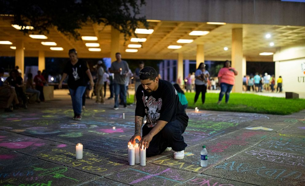 PHOTO: George Guerrero leaves candles at a makeshift memorial after a vigil at the University of Texas Permian Basin for the victims of the mass shooting in Odessa, Texas, Sept. 1, 2019.