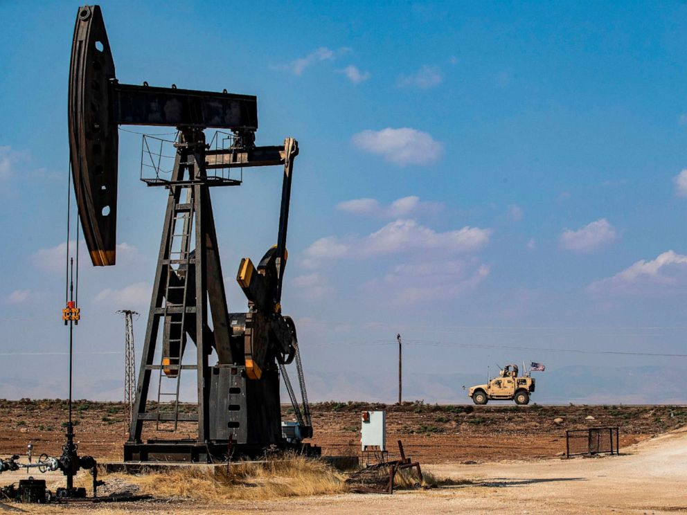 PHOTO: A U.S. military vehicle, part of a convoy arriving from northern Iraq, drives past an oil pump jack in the countryside of Syrias northeastern city of Qamishli, Oct. 26, 2019.