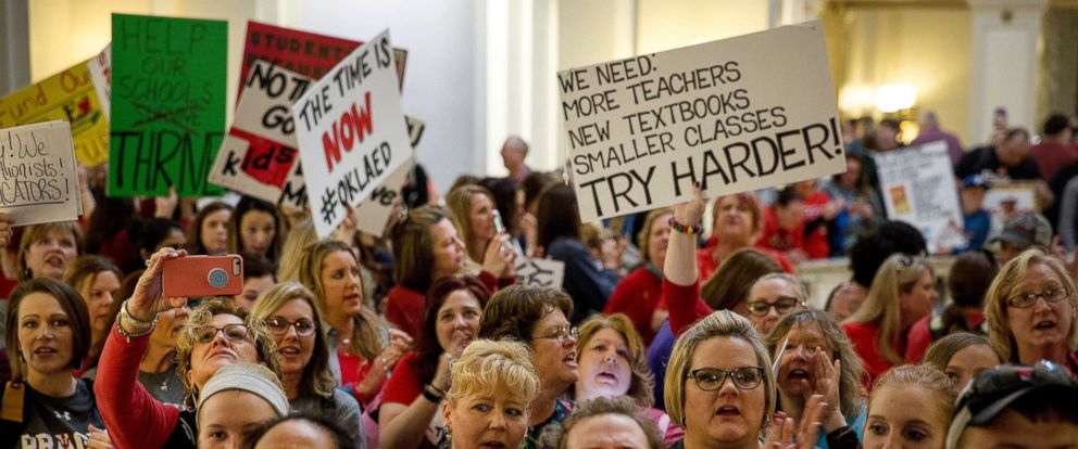 PHOTO: Teachers and demonstrators hold signs during a rally inside the Oklahoma State Capitol building in Oklahoma City, Okla., April 3, 2018.