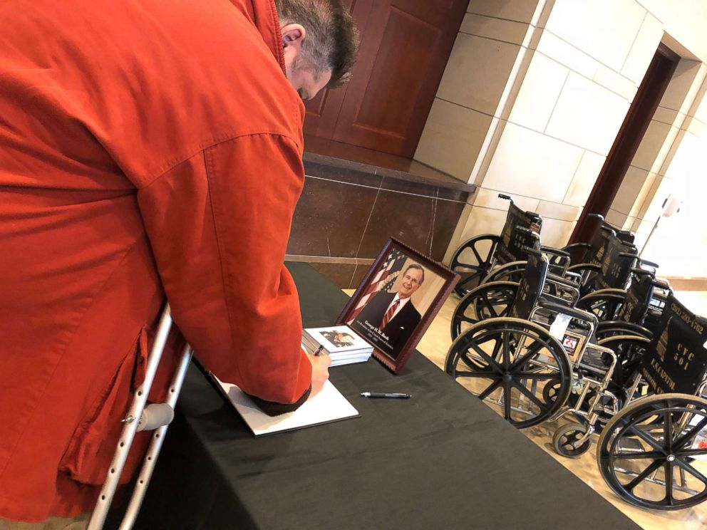PHOTO: Paul Smith, 52, of Tooele, Utah, signs a condolence book with a message for former President George H.W. Bush and his family as he leaves the U.S. Capitol, where Bush lies in state before his funeral service on Dec. 4, 2018.