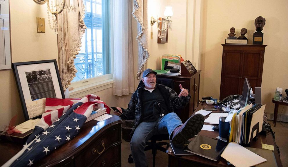PHOTO: A supporter of President Donald Trump sits inside the office of Speaker of the House Nancy Pelosi after protesters broached the U.S. Capitol in Washington, D.C., Jan. 6, 2021, as Congress met to certify the a 2020 presidential election.