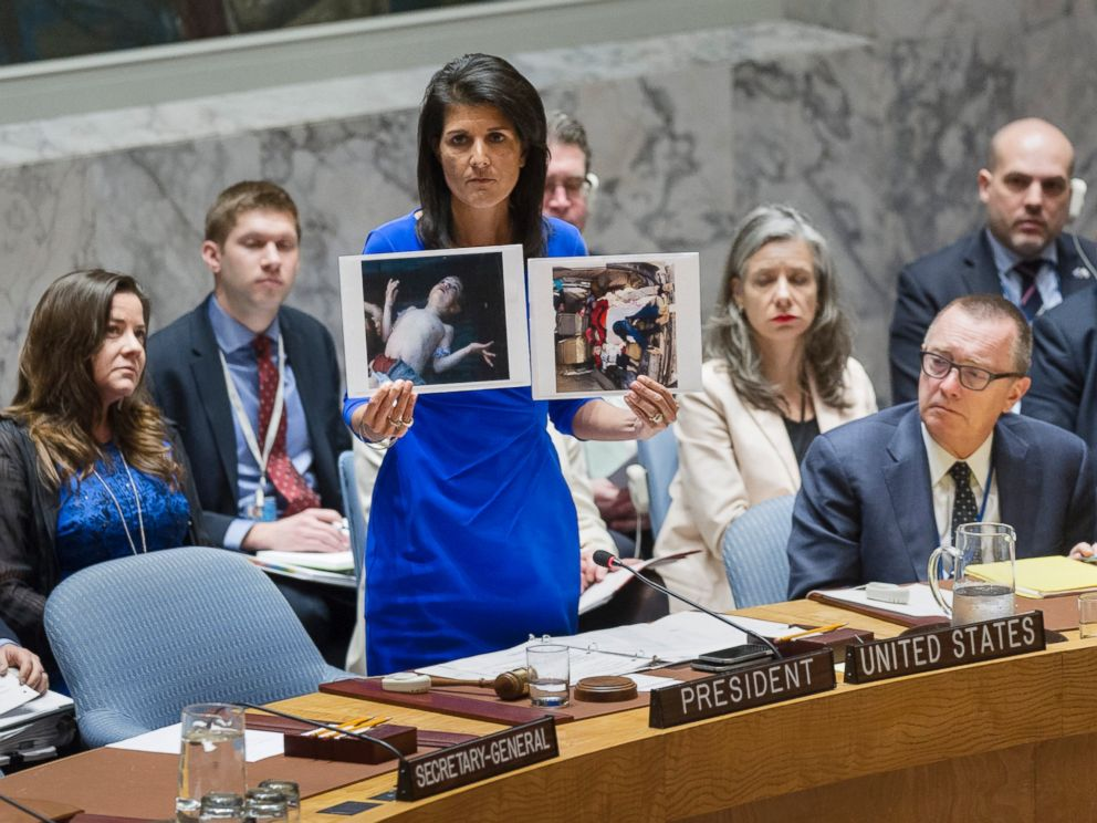 PHOTO: Nikki Haley, United States Permanent Representative to the UN, addresses the UN Security Council on April 5, 2017 in New York, while holding two photographs of Syrian children killed an alleged chemical attack.