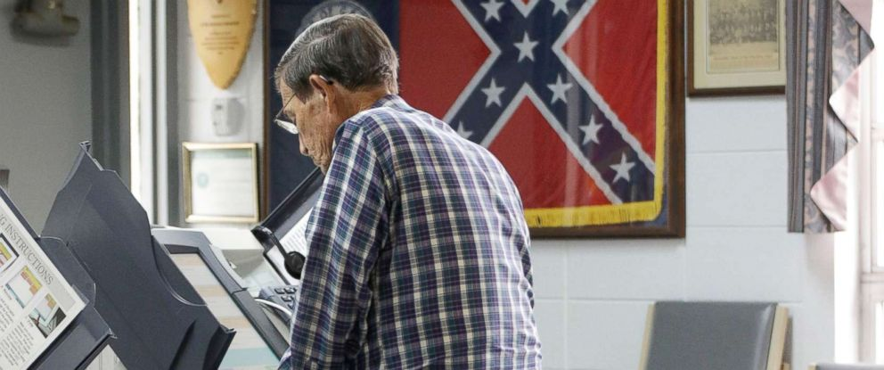 PHOTO: The 1956 Georgia state flag is displayed in a frame as George Farr votes at the Chickamauga Civic Center, May 22, 2018, in Chickamauga, Ga.