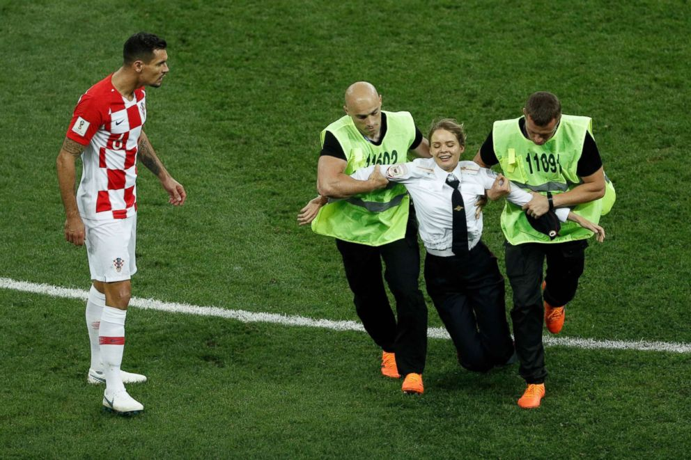 PHOTO: A striker is escorted out of the football pitch by security members during the Russia 2018 World Cup final football match between France and Croatia at the Luzhniki Stadium in Moscow on July 15, 2018.