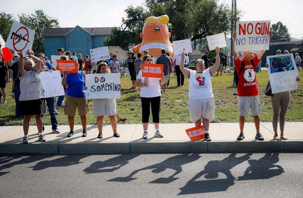 PHOTO: People gather to protest the arrival of President Donald Trump Aug. 7, 2019, outside Miami Valley Hospital after a mass shooting, in Dayton, Ohio.