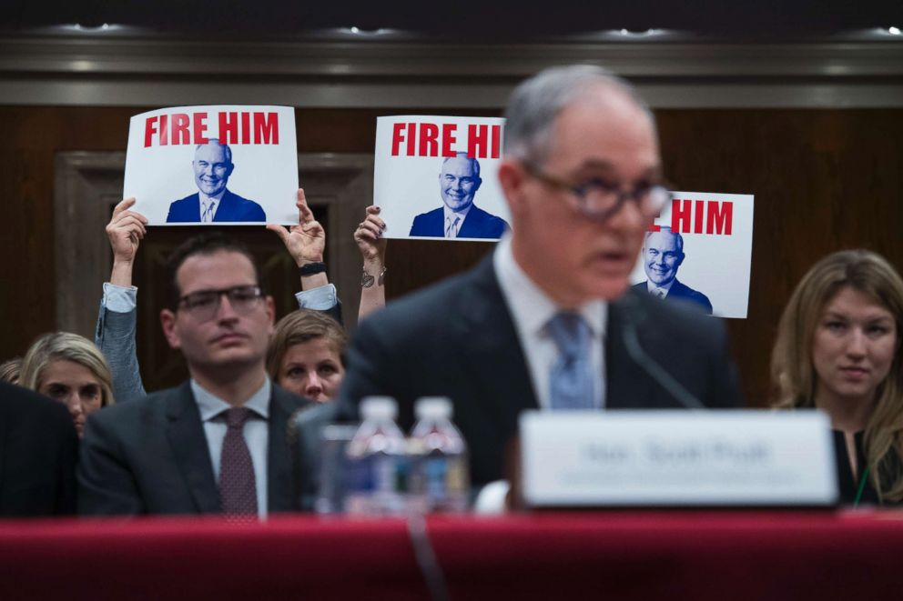 PHOTO: Protesters hold signs as Environmental Protection Agency Administrator Scott Pruitt testifies during a Senate Appropriations Interior, Environment, and Related Agencies Subcommittee hearing in Capitol Hill in Washington, D.C., May 16, 2018.