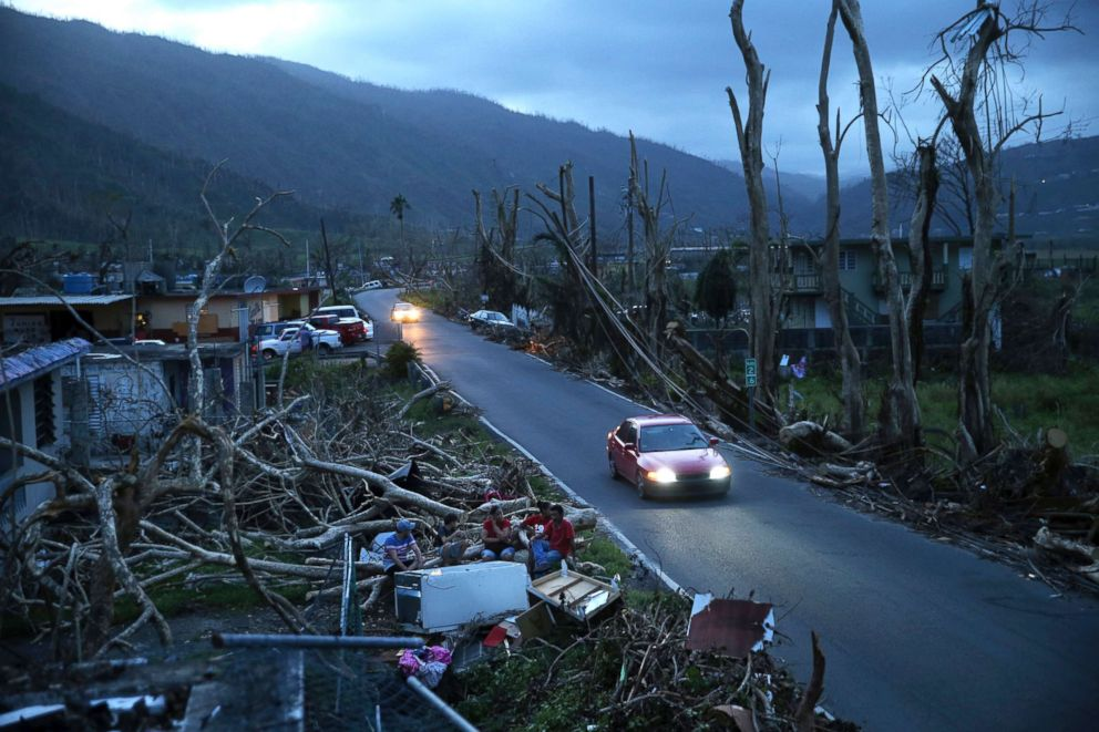 Neighbors sit on a couch outside their destroyed homes as sun sets in the aftermath of Hurricane Maria, in Yabucoa, Puerto Rico, Sept. 26, 2017.