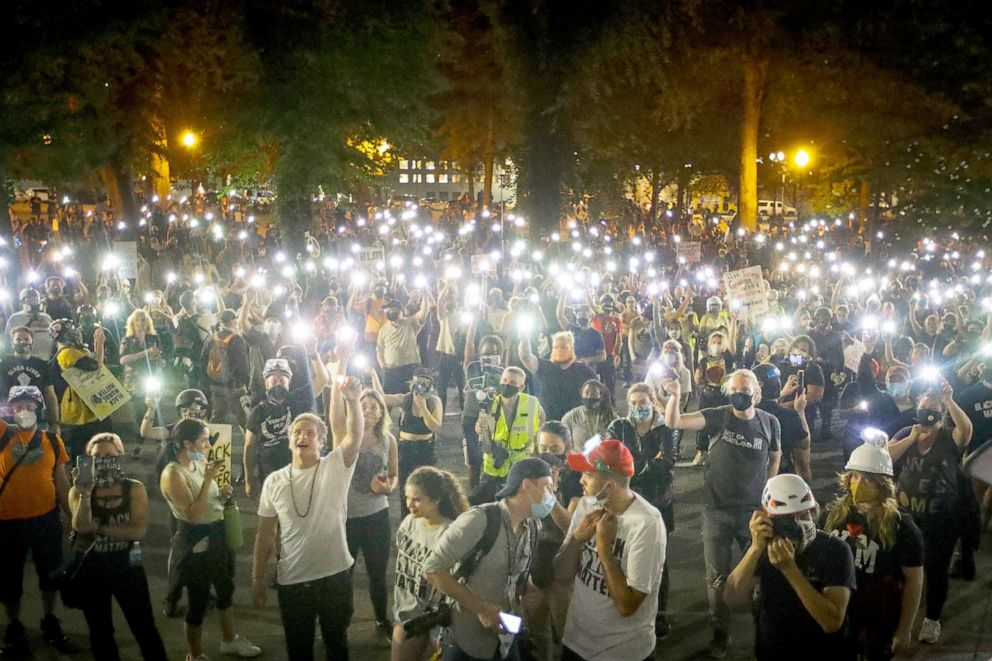 PHOTO: Demonstrators raise their cell phone lights as they chant slogans during a Black Lives Matter protest in Portland, Ore., July 29, 2020.