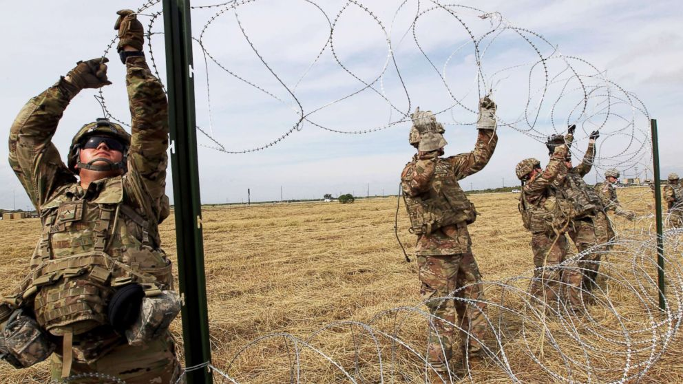 Army soldiers from Ft. Riley, Kansas, put up razor wire fence for an encampment to be used by the military near the U.S. Mexico border in Donna, Texas, Nov. 4, 2018.