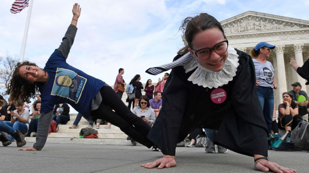 Stephanie Firestone, left, and Alice Wisbiski, right, both fans of Supreme Court Associate Justice Ruth Bader Ginsburg, do exercises on the steps of the Supreme Court in Washington, March 15, 2019, to celebrate Ginsburg's upcoming birthday 86th birthday.