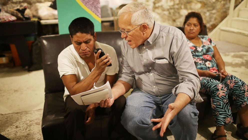 Ruben Garcia (C), director of the Annunciation House, speaks on a cell phone with a person from the Office of Refugee Resettlement as he sits with Cristian, who migrated from Guatemala, and Miriam, who migrated from Honduras as they try to track down their children after being released from U.S. Customs and Border Protection custody, June 25, 2018, in El Paso, Texas. Cristian and Miriam are part of a group of 32 parents that arrived at the Annunciation House migrant shelter as they wait to be reunited with their children.
