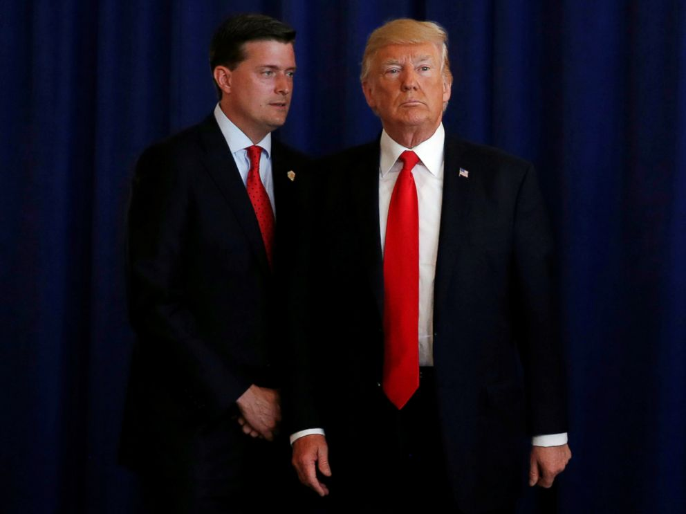 PHOTO: White House Staff Secretary Rob Porter (L) reminds President Donald Trump he had a bill to sign after he departed quickly following remarks at his golf estate in Bedminster, N.J., Aug. 12, 2017.