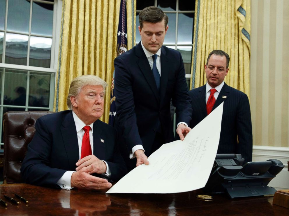 PHOTO: White House Staff Secretary Rob Porter, center, hands President Donald Trump a confirmation order for James Mattis as defense secretary, as White House Chief of Staff Reince Priebus, right, watches, Jan. 20, 2017 in Washington, D.C.