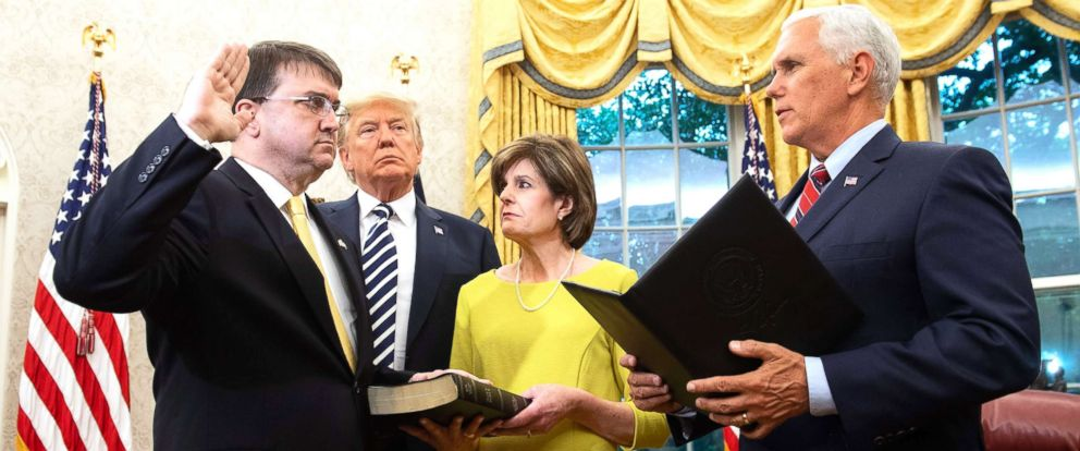 PHOTO: President Donald Trump stands alongside Robert Wilkie as he is sworn-in alongside his wife, Julia, as Secretary of Veterans Affairs by Vice President Mike Pence in the Oval Office of the White House, July 30, 2018.