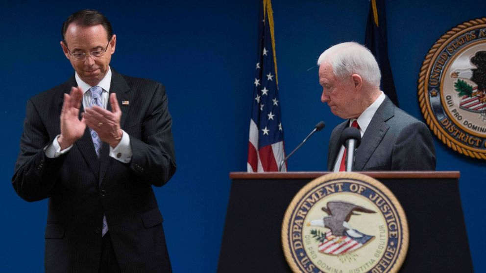 Deputy Attorney General Rod Rosenstein applauds after Attorney General Jeff Sessions, right, made an announcement on efforts to reduce transitional crime during a press conference at the U.S. Attorney's Office in Washington, Oct, 15, 2018.