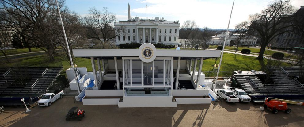 PHOTO: Construction workers walk by a reviewing stand for the upcoming presidential inauguration outside of the White House in Washington, Jan. 15, 2017.