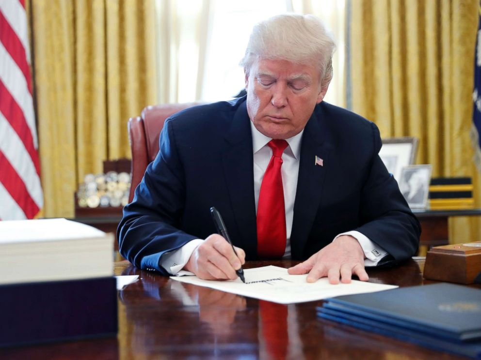 PHOTO: President Donald Trump signs the $1.5 trillion tax overhaul plan in the Oval Office of the White House in Washington, Dec. 22, 2017.