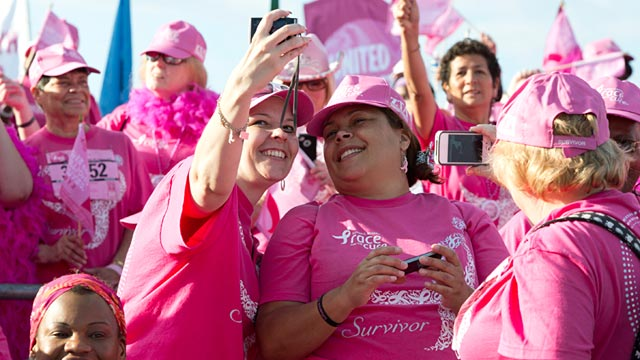 PHOTO: Breast cancer survivors take pictures of each other during the Susan G. Komen Foundations 2012 Race for the Cure in Washington, June 2, 2012.