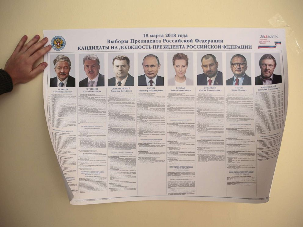 PHOTO: A member of a local electoral commission attaches a broadsheet with information about the candidates during preparations for the upcoming presidential election at a polling station in St. Petersburg, March 17, 2018.
