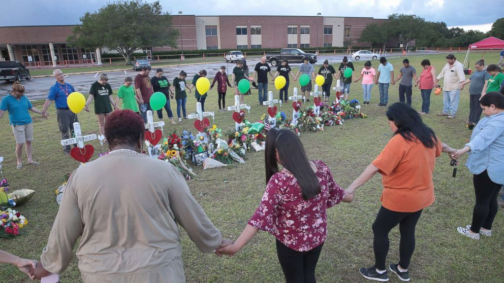 Mourners pray around a memorial in front of Santa Fe High School, May 21, 2018, in Santa Fe, Texas. The makeshift memorial honors the victims of the May 18 shooting when 17-year-old student Dimitrios Pagourtzis entered the school with a shotgun and a pistol and opened fire, killing 10 people.