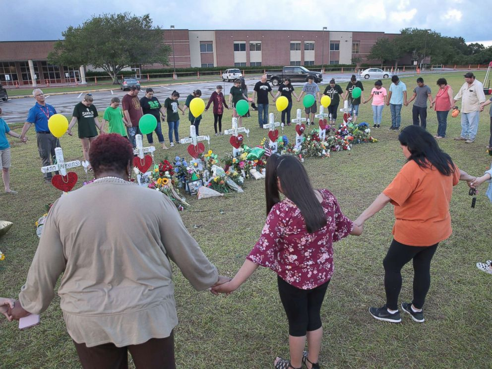 PHOTO: Mourners pray around a memorial in front of Santa Fe High School, May 21, 2018, in Santa Fe, Texas.
