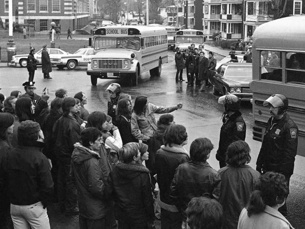 PHOTO: White students, who walked out of Bostons Hyde Park High School, stand along the curb and jeer school buses carrying blacks home from the school, Dec. 12, 1974.