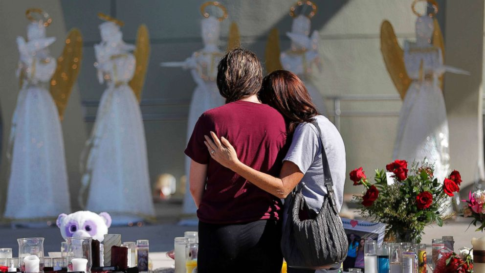 People comfort each other at a public memorial for the victims of the shooting at Marjory Stoneman Douglas High School, in Parkland, Fla., Feb. 16, 2018.