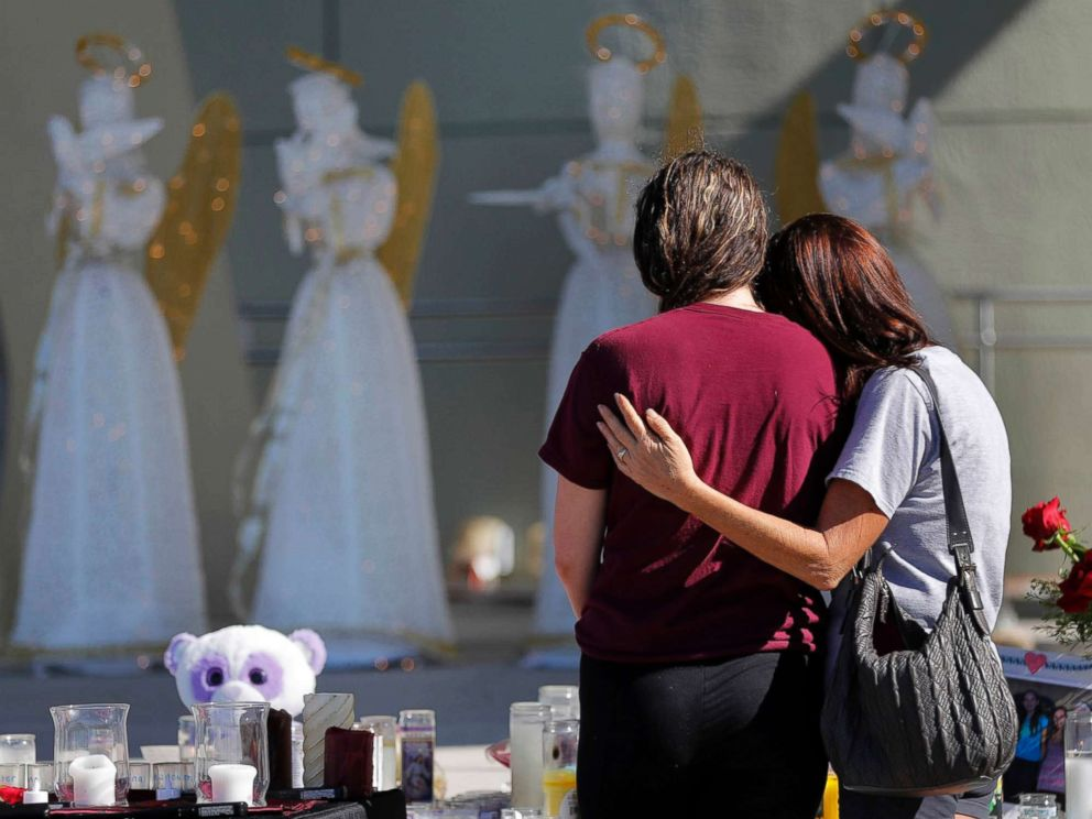 PHOTO: People comfort each other at a public memorial for the victims of the shooting at Marjory Stoneman Douglas High School, in Parkland, Fla., Feb. 16, 2018.