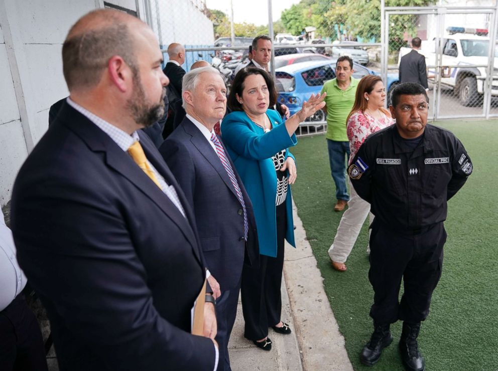 PHOTO: U.S. Attorney General Jeff Sessions, center, and U.S. Ambassador to El Salvador Jean Elizabeth Manes, right, stop to look across the courtyard during a tour of local police station and detention center in San Salvador, El Salvador, July 27, 2017.