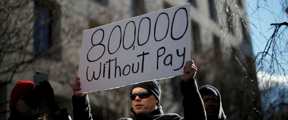 PHOTO: A demonstrator holds a sign, signifying hundreds of thousands of federal employees who will not be receiving their paychecks as a result of the partial government shutdown, during a rally to end the shutdown in Washington D.C., Jan. 10, 2019.
