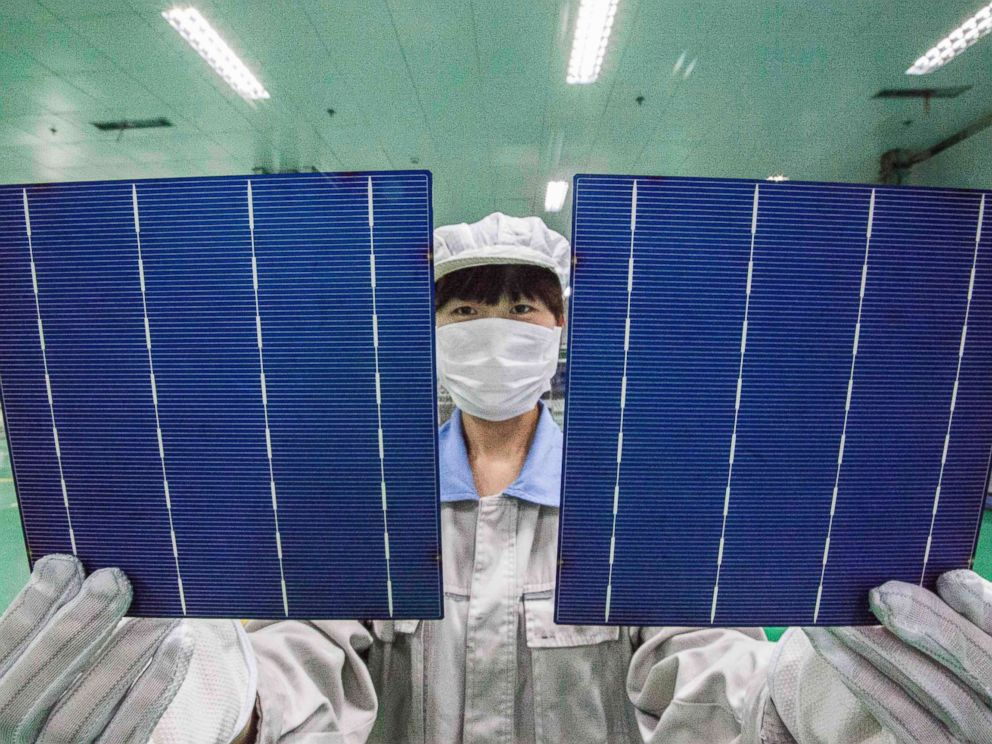 PHOTO: A Chinese worker shows photovoltaic cells to be used to make solar panels at a solar manufacturing plant in Lianyungang city, east Chinas Jiangsu province, China, Oct. 21, 2014.