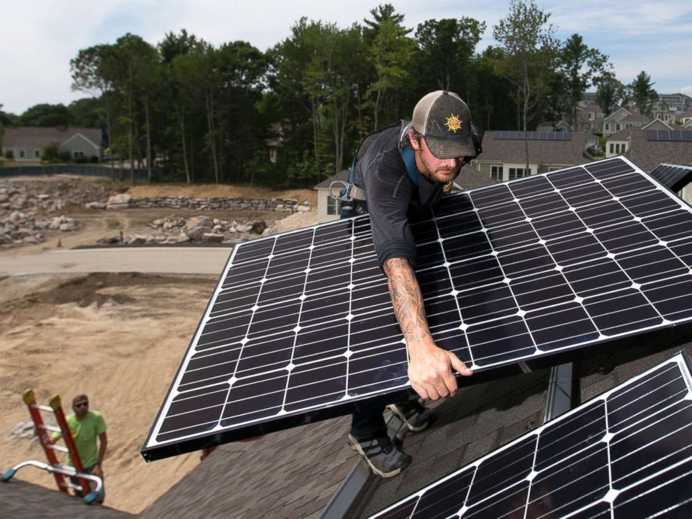 PHOTO: A man installs solar panels on a home in Falmouth, Maine, Aug. 2, 2017.