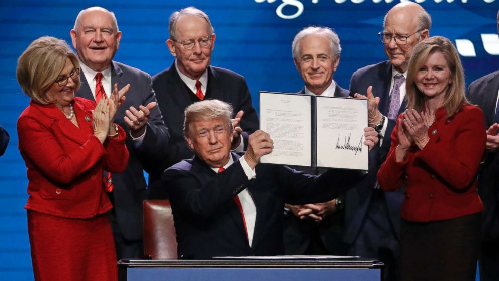President Donald Trump holds up an executive order after signing it at the American Farm Bureau Federation annual convention Monday, Jan. 8, 2018, in Nashville, Tenn., as, from left, Rep. Diane Black, R-Tenn., Agriculture Secretary Sonny Perdue, Sen. Lamar Alexander, R-Tenn., Sen. Bob Corker, R-Tenn., Sen. Pat Roberts, R-Kan., and Rep. Marsha Blackburn, R-Tenn., applaud.
