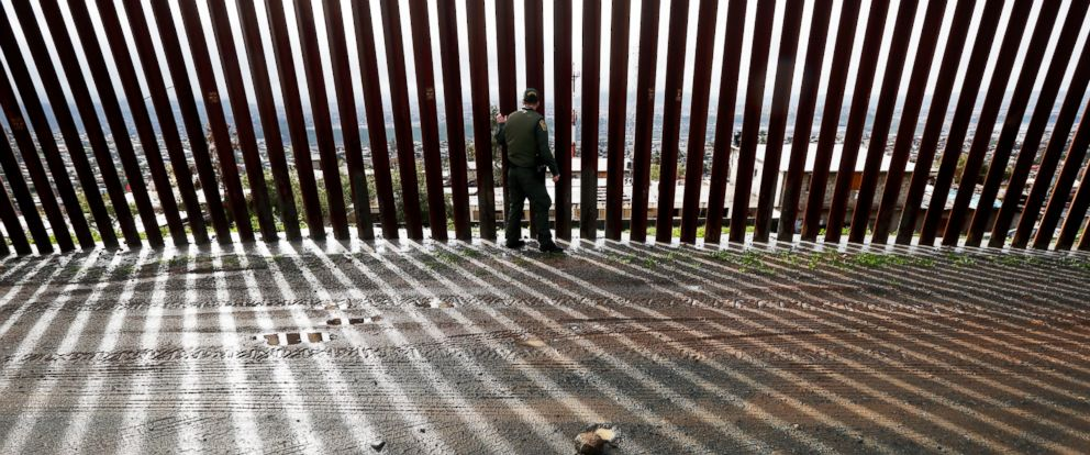 PHOTO: Border Patrol agent Vincent Pirro touches a section of the border wall separating Tijuana, Mexico, behind, from San Diego, Feb. 5, 2019, in San Diego.
