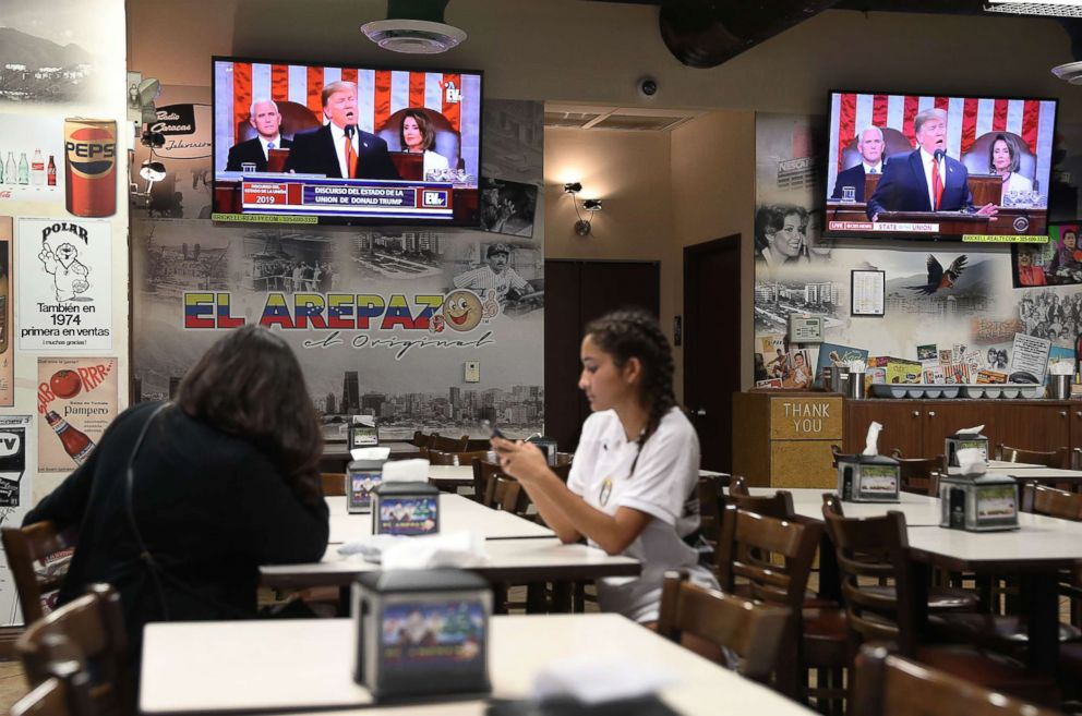 PHOTO: Customers visit the El Original EL Arepazo restaurant as a television broadcasts President Donald Trump as he delivers his State of the Union address to a joint session of the U.S. Congress on Capitol Hill on Feb. 5, 2019, in Doral, Fla.