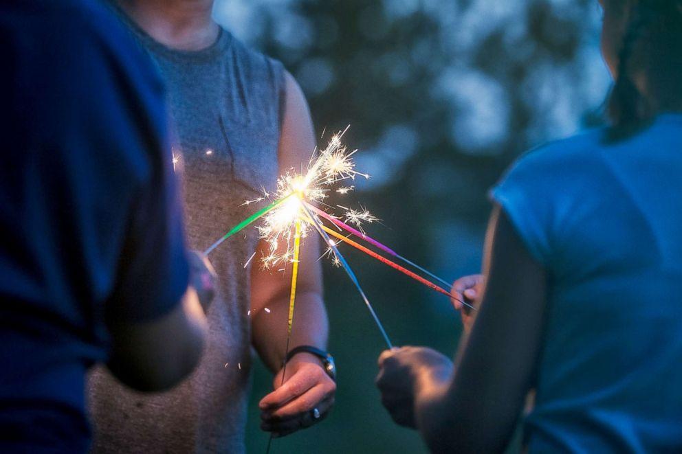 PHOTO: People light sparklers.