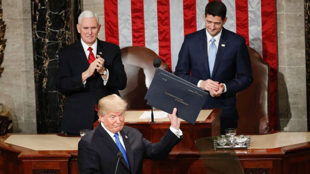 President Donald Trump holds up copies of his speech upon arrival and before delivering his State of the Union address to a joint session of Congress on Capitol Hill in Washington, Jan. 30, 2018.