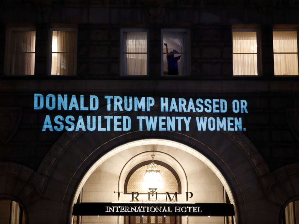 PHOTO: A person waves from a window as UltraViolet, a national womens group, projects a message on the 12th Street side of the Trump International Hotel before President Donald Trump gives his State of the Union Address, Jan. 30, 2018, in Washington.