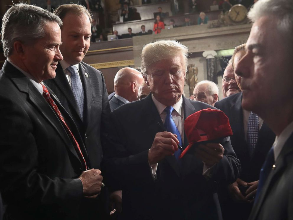 PHOTO: President Donald Trump signs a hat on his way out of the House chamber and after finishing his first State of the Union address, Jan. 30, 2018 in Washington, DC.