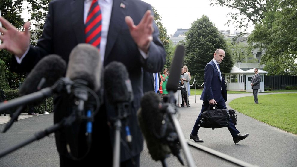 Senior Advisor to the President Stephen Miller walks behind President Donald Trump as he talks to reporters before they depart the White House, June 8, 2018 in Washington.