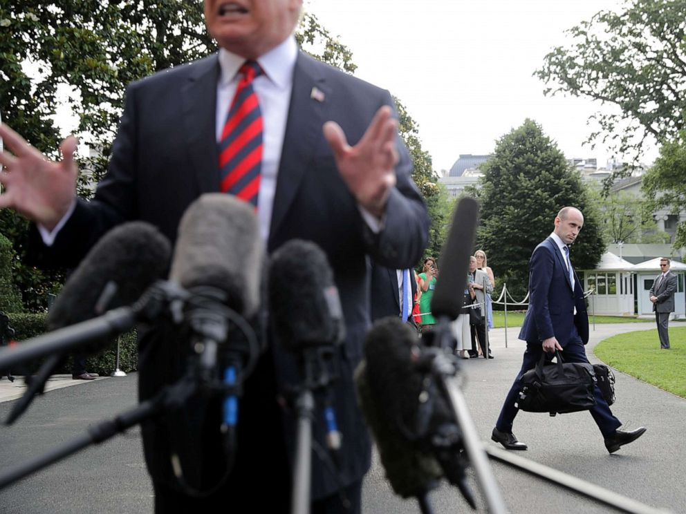 PHOTO: Senior Advisor to the President Stephen Miller walks behind President Donald Trump as he talks to reporters before they depart the White House, June 8, 2018 in Washington.