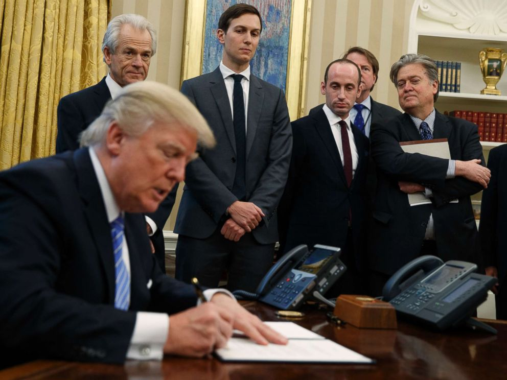PHOTO: From left, Reince Priebus, National Trade Council adviser Peter Navarro, Jared Kushner, policy adviser Stephen Miller, and chief strategist Steve Bannon watch as President Donald Trump signs an executive order on Jan. 23, 2017, in Washington.