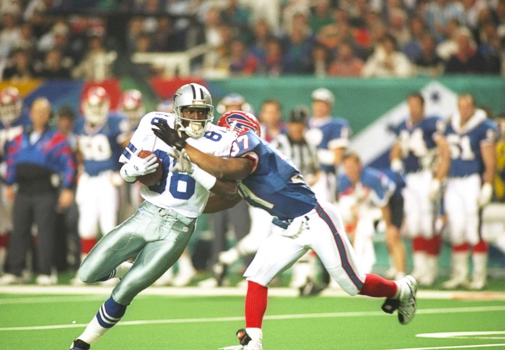 Wide receiver Michael Irvin of the Dallas Cowboys (left) moves the ball as Buffalo Bills defensive back Nate Odomes attempts to tackle him during Super Bowl XXVIII at the Georgia Dome in Atlanta.The Cowboys won the game, 30-13.