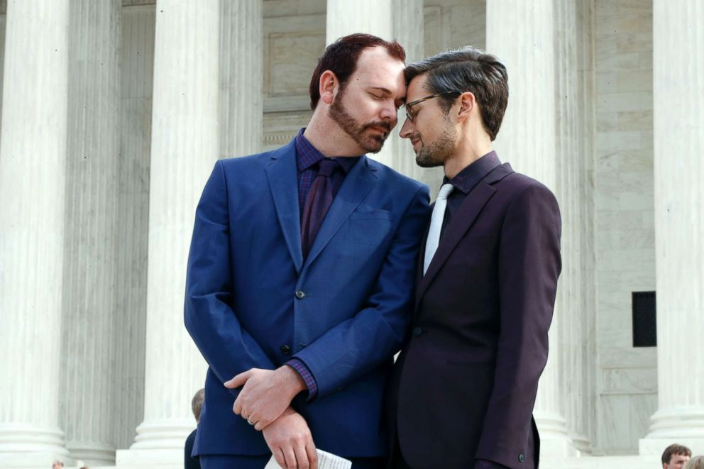 Charlie Craig, left, and David Mullins touch foreheads after leaving the Supreme Court in Washington, DC, Dec. 5, 2017.