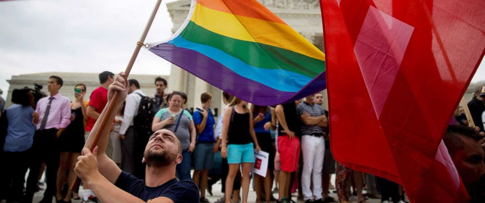 PHOTO: A demonstrator in support of same-sex marriage waves a rainbow colored flag after the same-sex marriage ruling outside the U.S. Supreme Court in Washington, D.C., June 26, 2015.