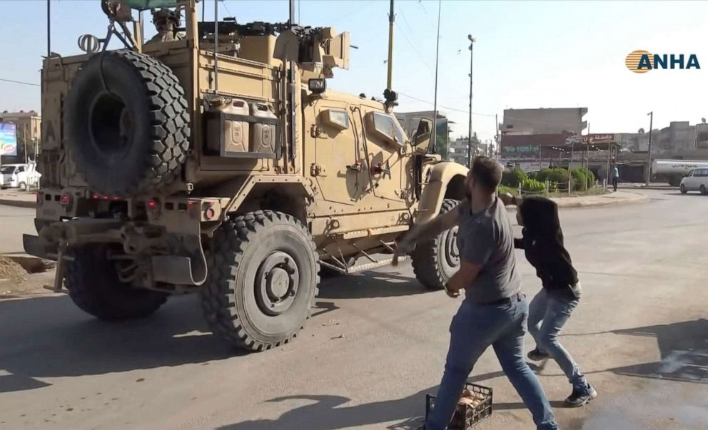 PHOTO: In this frame grab provided by Hawar News, ANHA, the Kurdish news agency, residents who are angry over the U.S. withdrawal from Syria hurl potatoes at American military vehicles in the town of Qamishli, northern Syria, Monday, Oct. 21, 2019.