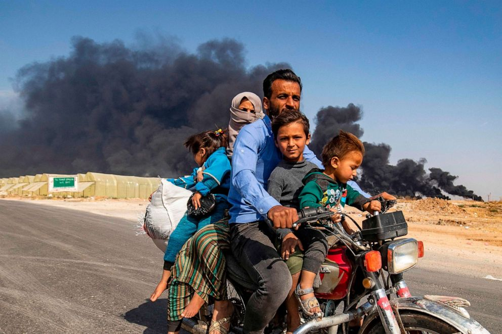 PHOTO: Displaced people, fleeing from the countryside of the Syrian Kurdish town of Ras al-Ain along the border with Turkey, ride a motorcycle together along a road on the outskirts of the nearby town of Tal Tamr on Oct. 16, 2019.